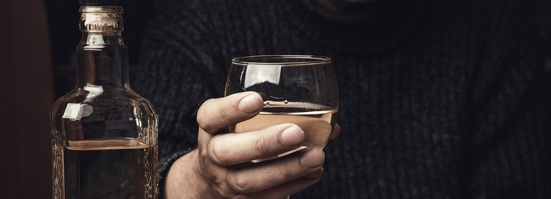 Person holding a glass of alcohol with a bottle next to them.