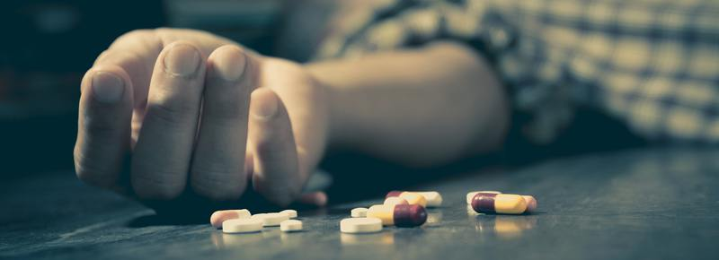 Person lying on the back with an open hand and pills nearby.