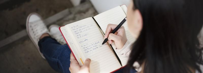 Person writing in a notebook.