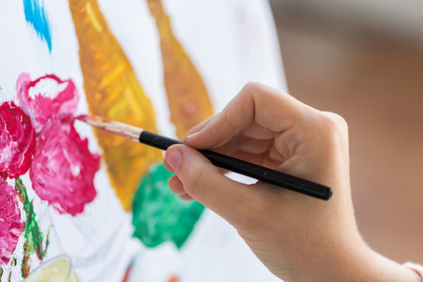 Person painting a canvas as part of therapy.