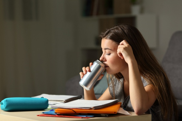 Teen girl drinking a beverage while studying.