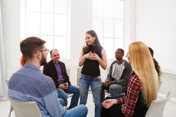 Group of people talking while sitting in a support group circle.