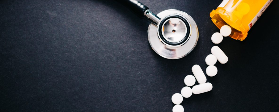 Norco and vicodin pills spilled over next to a stethoscope