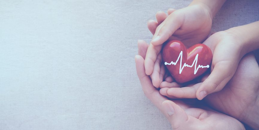 Patient holds a heart in their hands to represent insurance and health