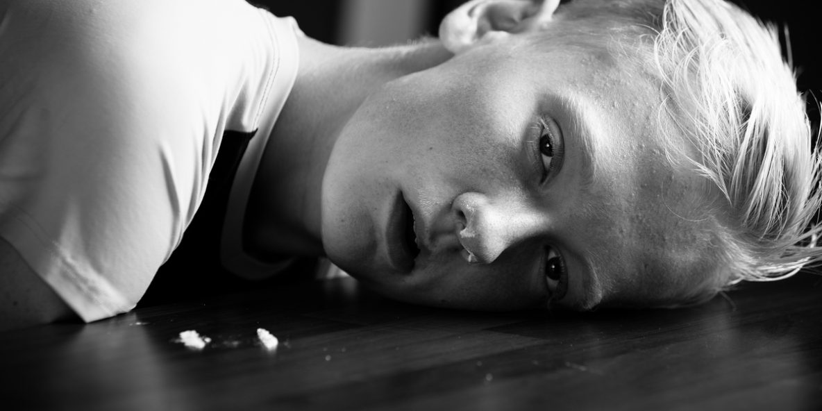 A boy laying on the floor after a methadone overdose due to an addiction