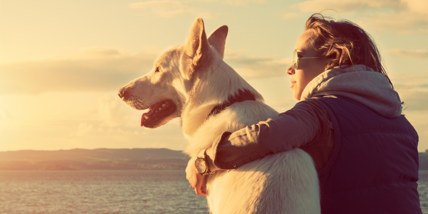 Woman in recovery sitting in front of a body of water during sunset with her therapy dog
