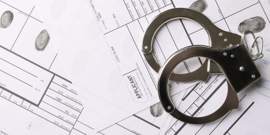 Handcuffs on top of paperwork from drug arrests in Illinois to be expunged