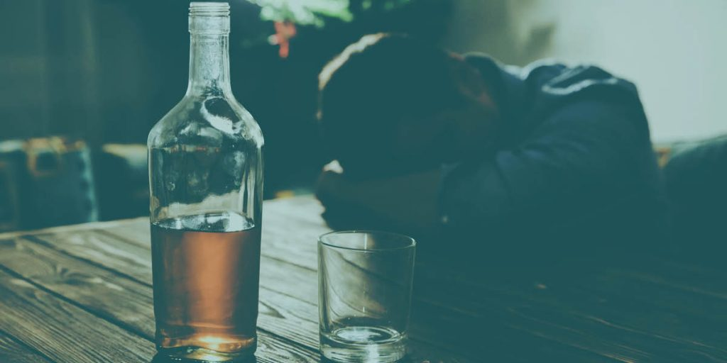 Man going through alcohol detox at home sits next to half a bottle of liquor